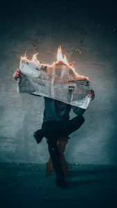 Person with burning newspaper